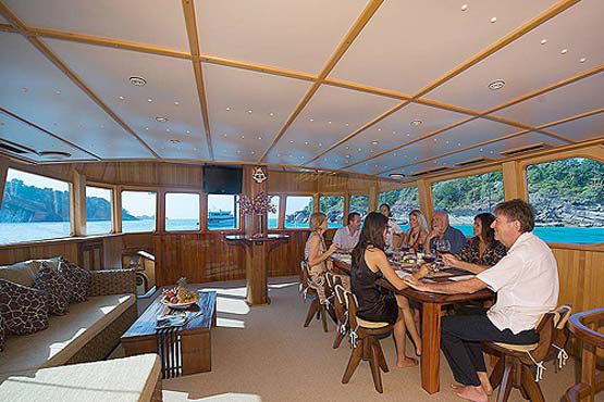 Luxury Sailing & Motor Catamaran dining for eight in the saloon