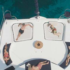 Luxury Sailing & Motor Catamaran sunbathing on the foredeck