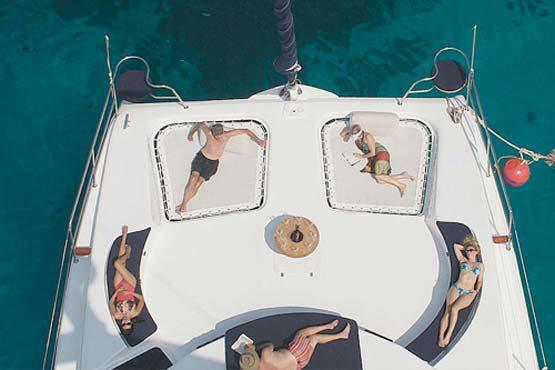 Luxury Sailing & Motor Catamaran sunbathing on the foredeck